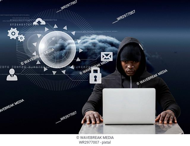 Hacker using a laptop in front of digital graphics