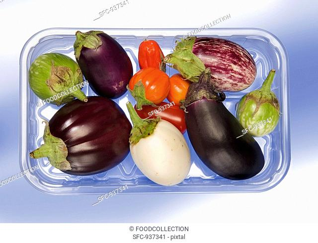 Various types of aubergines in a plastic tray