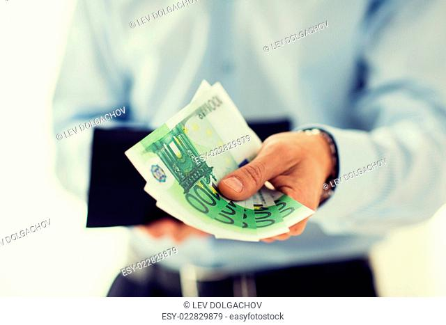 people, business, finances and money concept - close up of businessman hands holding open wallet with euro cash