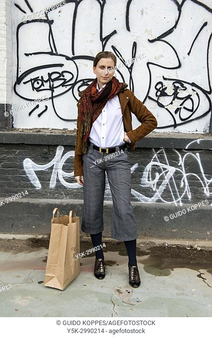 Tilburg, Netherlands. Portrait gender biased woman, wearing men's fashion inside an industrial environment with street art and graffiti painted walls