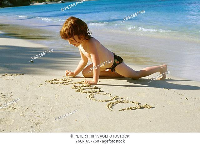 Child writing in sandy beach