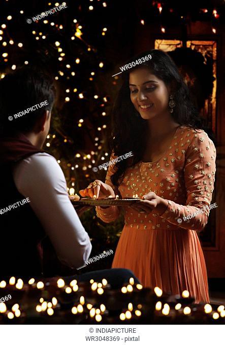 Couple arranging oil lamps on diwali