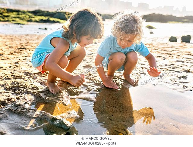 Little boy and girl playing together on the beach