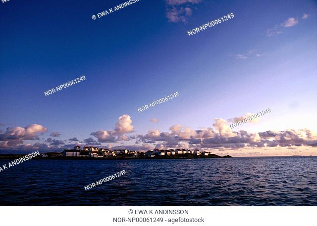 A cloudy sky above a town by the sea