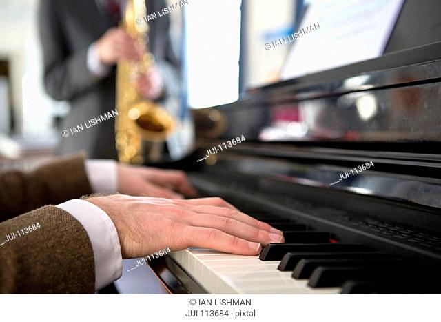 Close up music teacher playing piano with high school student playing saxophone in background