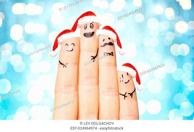 family, holidays, christmas and body parts concept - close up of hand with four fingers in santa hats with smiley faces over blue lights background
