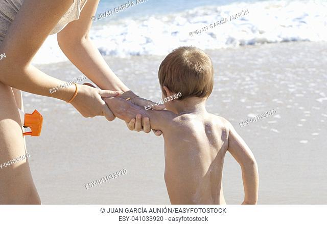 Mother applying sunblock cream to her little son on back. Idyllic beach background