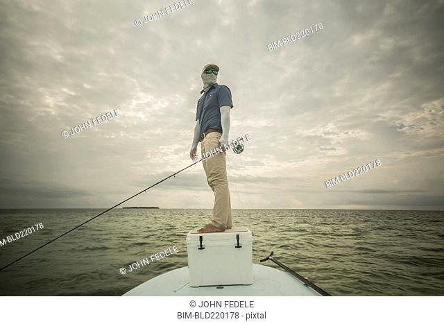 Caucasian fisherman standing on boat