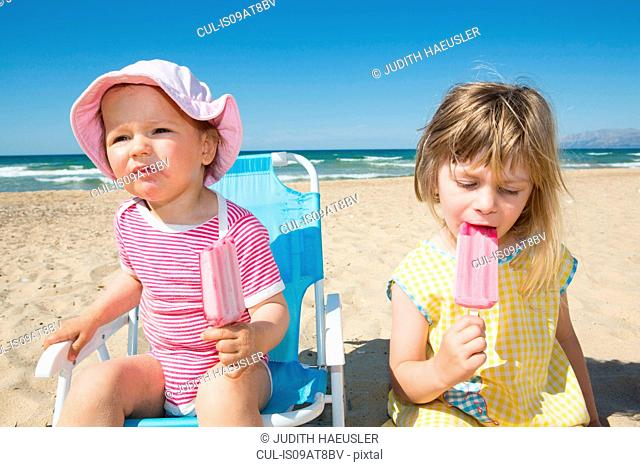 Female toddler and sister eating ice lollies on beach