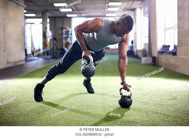 Man doing plank with kettlebells in gym