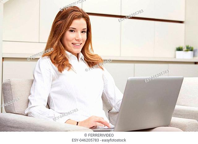 Smiling happy woman sitting on the sofa and using laptop
