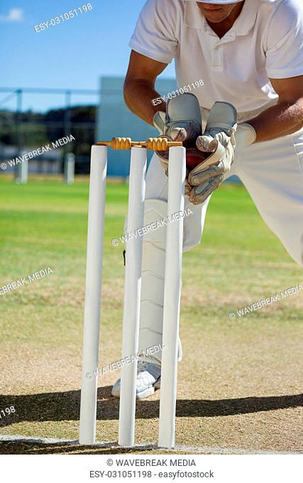 Low section of wicketkeeper catching ball behind stumps