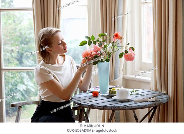 Woman arranging roses in vase