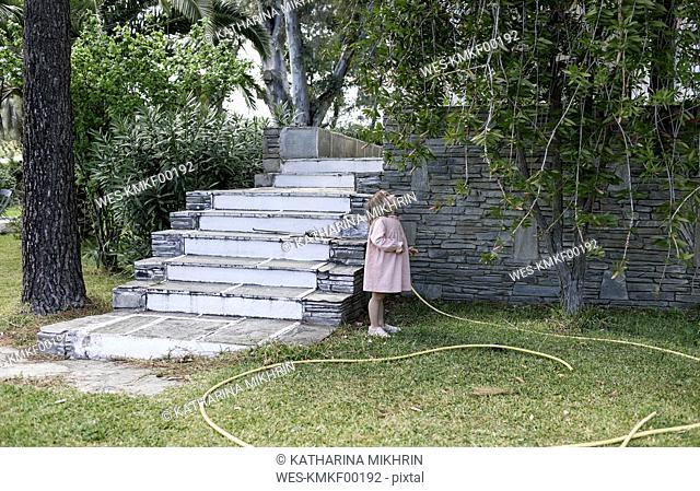 Little girl standing in garden looking up to tree