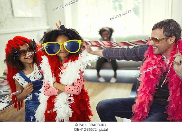 Portrait father and daughters playing dress up with oversized sunglasses and feather boas