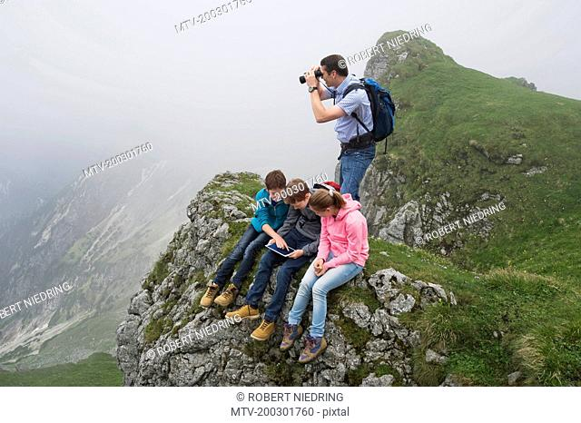 Father teenage kids in mountains iPad computer