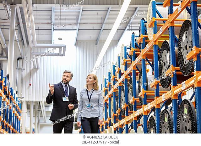 Businessman and businesswoman touring fiber optic factory floor