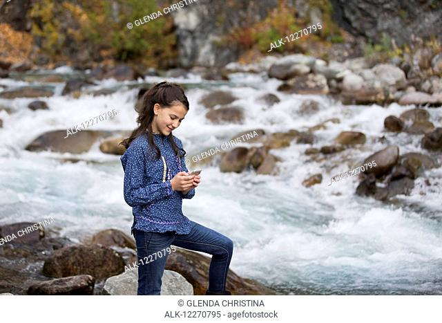 Tween Inupiat Eskimo girl in a traditional native kuspuk dress texting with cell phone near Hatcher Pass, Southcentral Alaska, Autumn