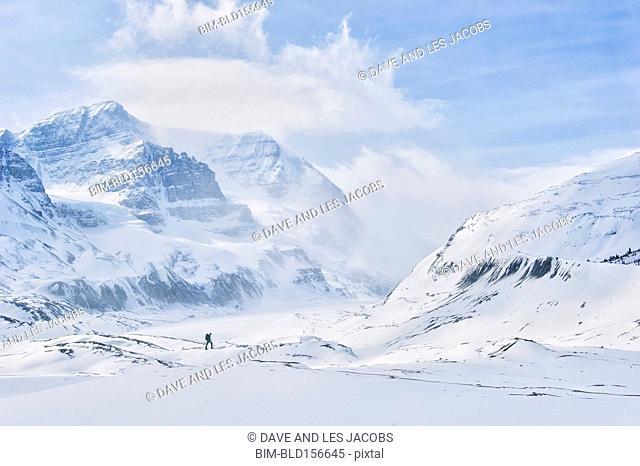 Caucasian hiker walking in snowy mountains