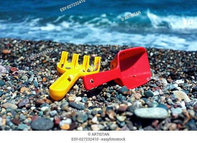 Children toy yellow rake and red shovel on a beach and sea behind