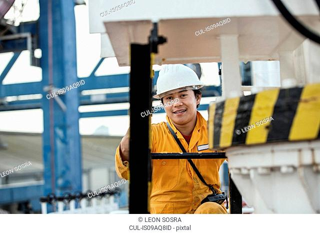 Portrait of crane driver looking up from control panel at dock