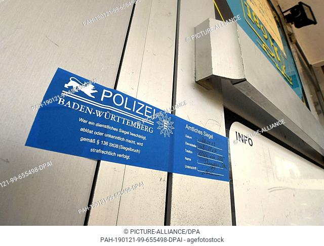 21 January 2019, Baden-Wuerttemberg, Karlsruhe: A police seal is attached to the entrance door of a bar in Karlsruhe. A 39-year-old man was shot dead in the bar...