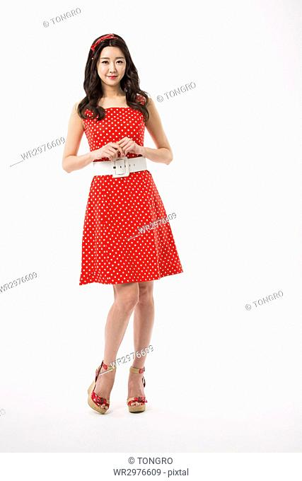 Young smiling woman in retro-style dress standing