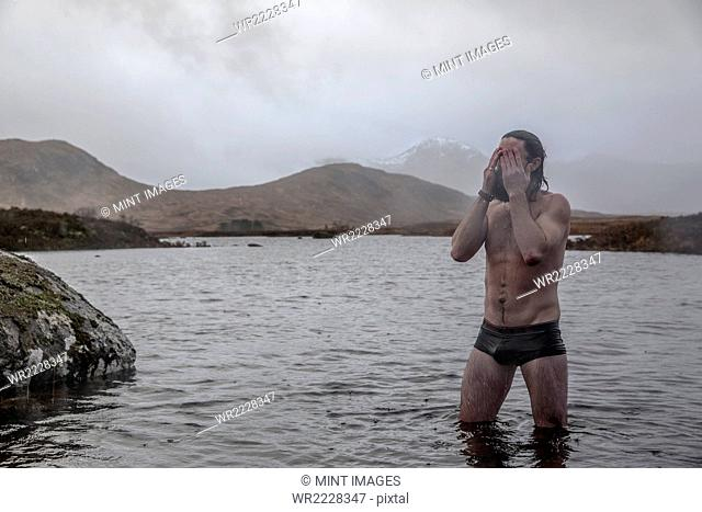 A man standing thigh deep in sea water in swimming trunks wiping water from his eyes
