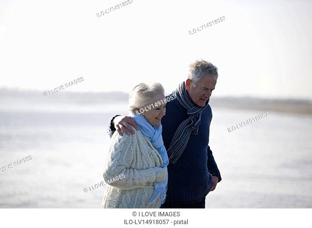 A senior couple walking along a beach, embracing