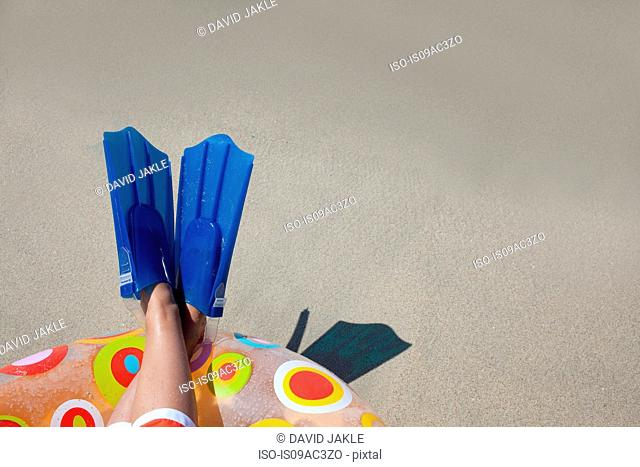 Young boys legs and flippers on rubber ring