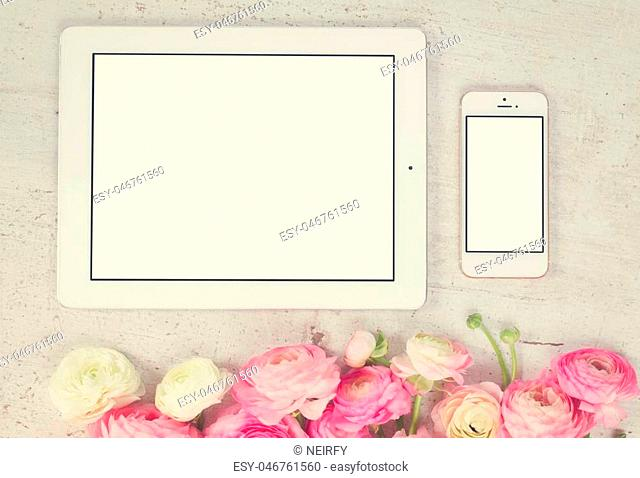 Pink and white ranunculus flowers styled flat lay scene with tablet and mobile, retro toned