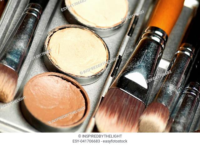 Professional cosmetic. Cream concealer palette in metal case. Expensive makeup brushes made of special fibers to work with creamy textures
