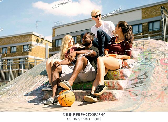 Four male and female basketball friends sitting chatting in city skatepark