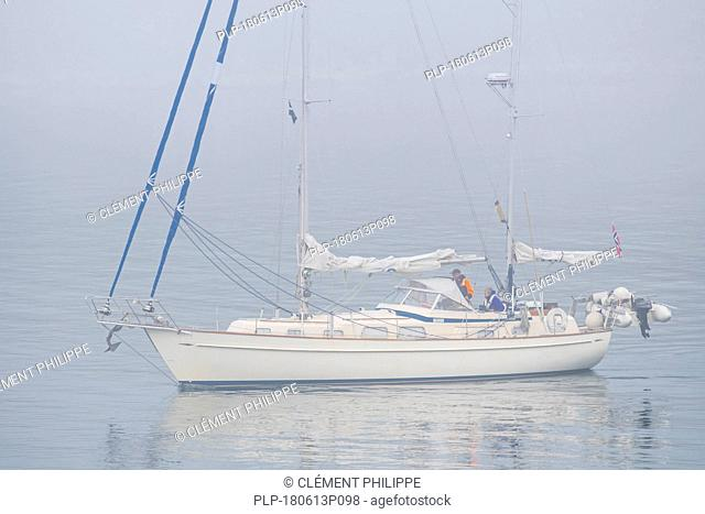 Sailboat / sailing boat / yacht with lowered sails at sea during bad visibility due to thick fog / dense mist
