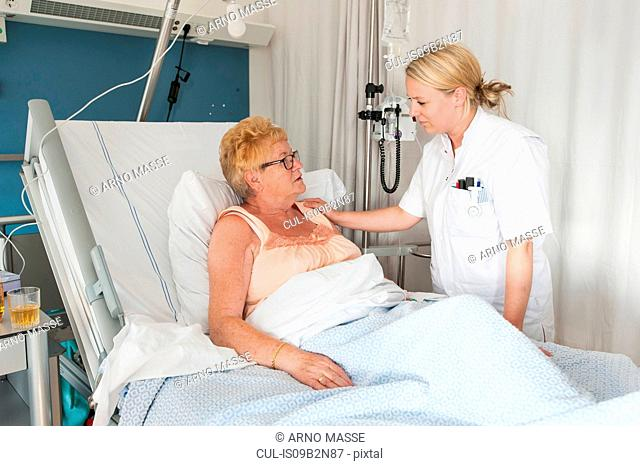 Nurse tending to patient in hospital bed