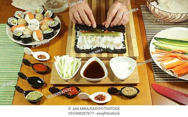 Rolling vegetarian Sushi roll with vegetable and sesame seeds