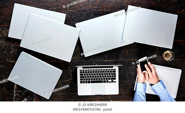 Man's hands using smartphone on table with seven laptops, top view