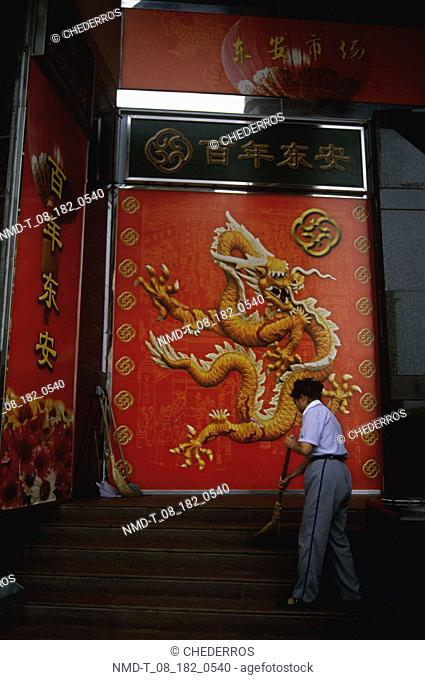 Side profile of a young man cleaning a staircase in front of a dragon engraved on a wall, China