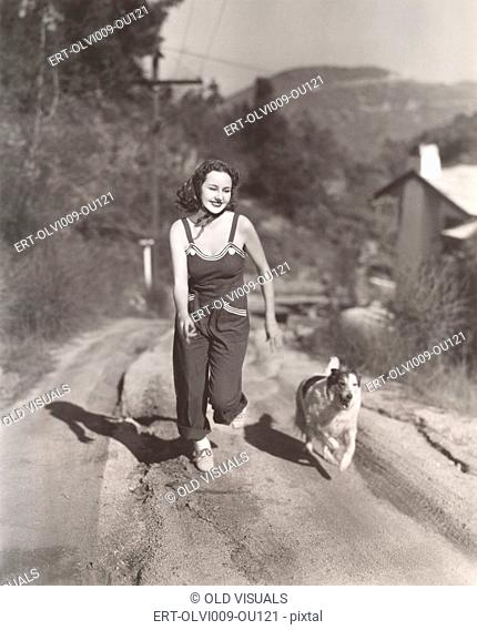 Woman running on dirt road with her dog