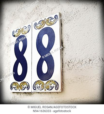 Number eighty-eight glazing on tiles from Manises, placed on the entrance wall of a house in La Cañada, Valencia, Valencia, Spain