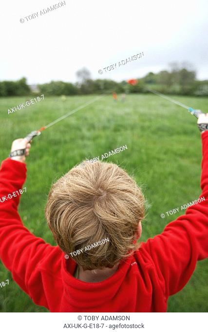 Young boy launching red kite in a grassy field