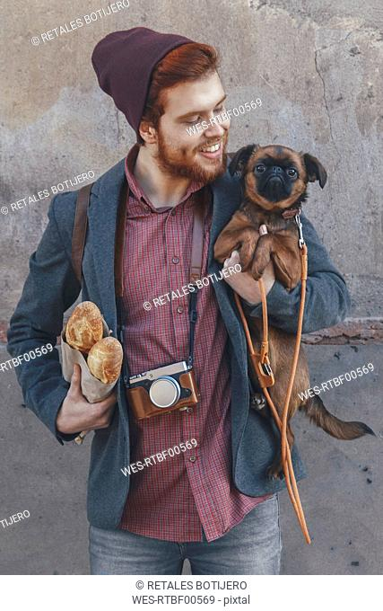 Smiling young man holding dog