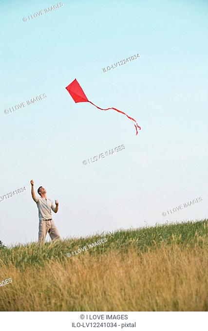 A young man flying a red kite