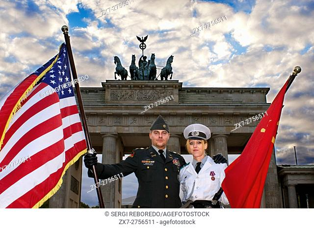 Actors dressed as American and Soviet soldiers pose for photos with tourists in front of the Brandenburg Gate in Berlin, one of the Cold War's most iconic...