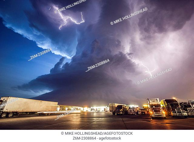 Amazing supercell storm during twilight nears a York Nebraska truck stop on I80 as it spits out lightning, June 17, 2009