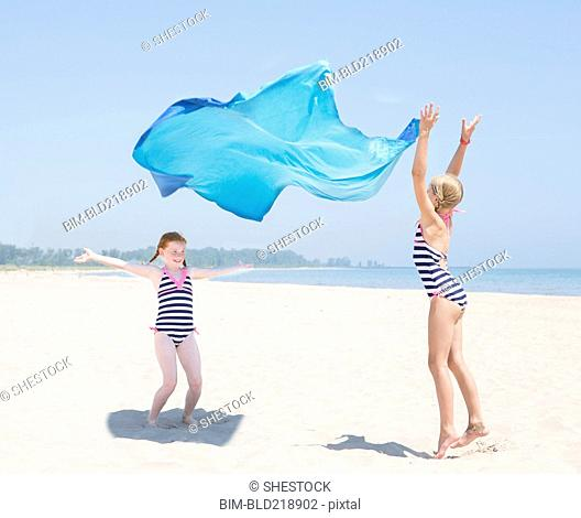 Caucasian girls playing with fabric on beach