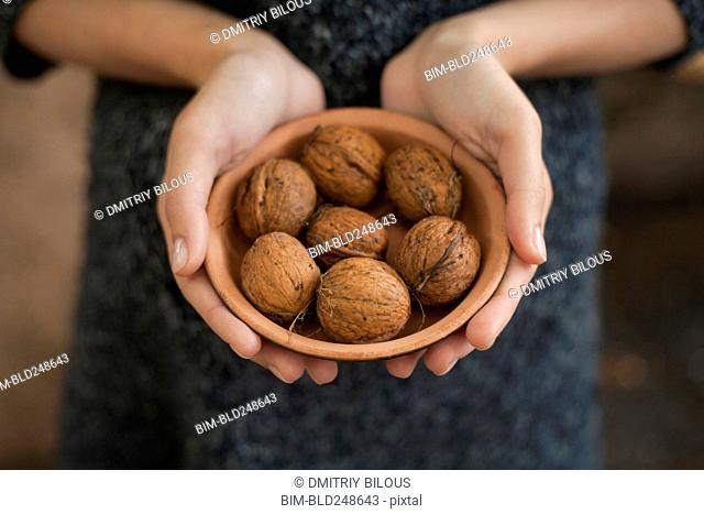 Hands holding bowl of walnuts