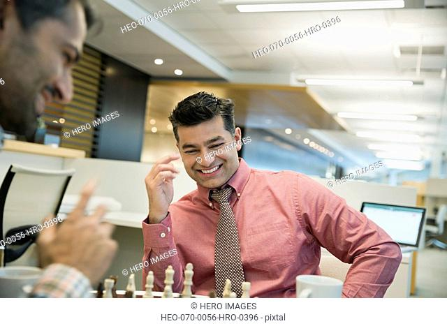 Businessman playing chess with male colleague in office