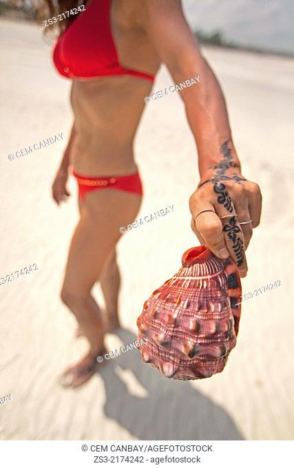 Woman holding a sea shell, Jambiani, Zanzibar Island, Tanzania, Indian Ocean, East Africa