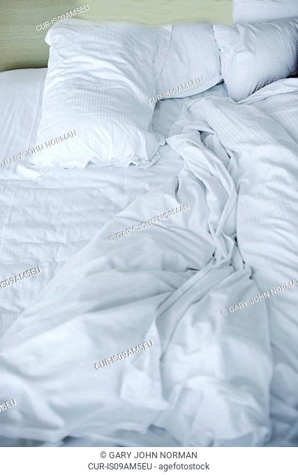 Unmade double bed with white pillows and duvet
